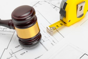 Judge gavel with measure tape above construction blueprint