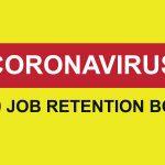 yellow sign which reads Coronavirus £1000 Job retention bonus
